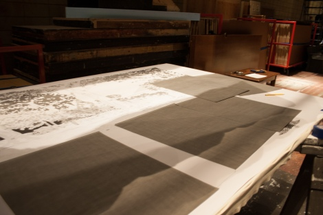 photo of graphite paper sheets on top of the paper mural outline.